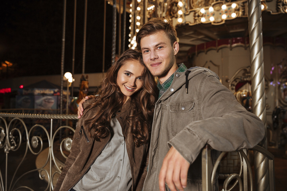 Portrait of couple in amusement park. looking at camera. smiling. hug