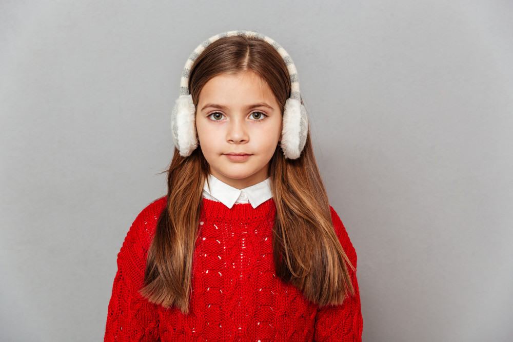 Portrait of cute little girl in red sweater and earmuffs