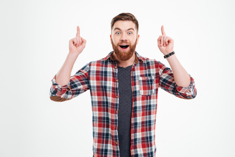 Portrait of excited bearded man in checkered shirt pointing fingers up over white background
