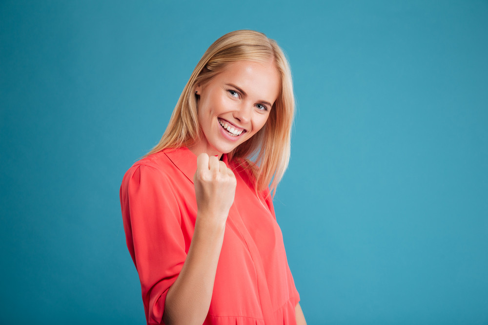 Portrait of excited delighted young woman in red dress celebrating success isolated on a blue background