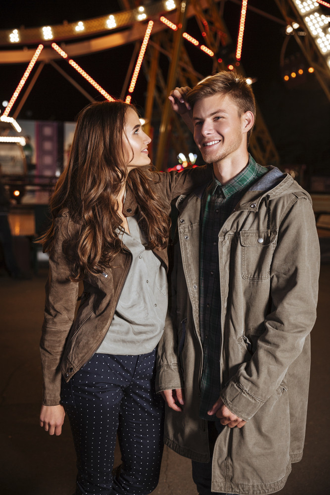 Portrait of fashion couple in amusement park. girl looking for a guy