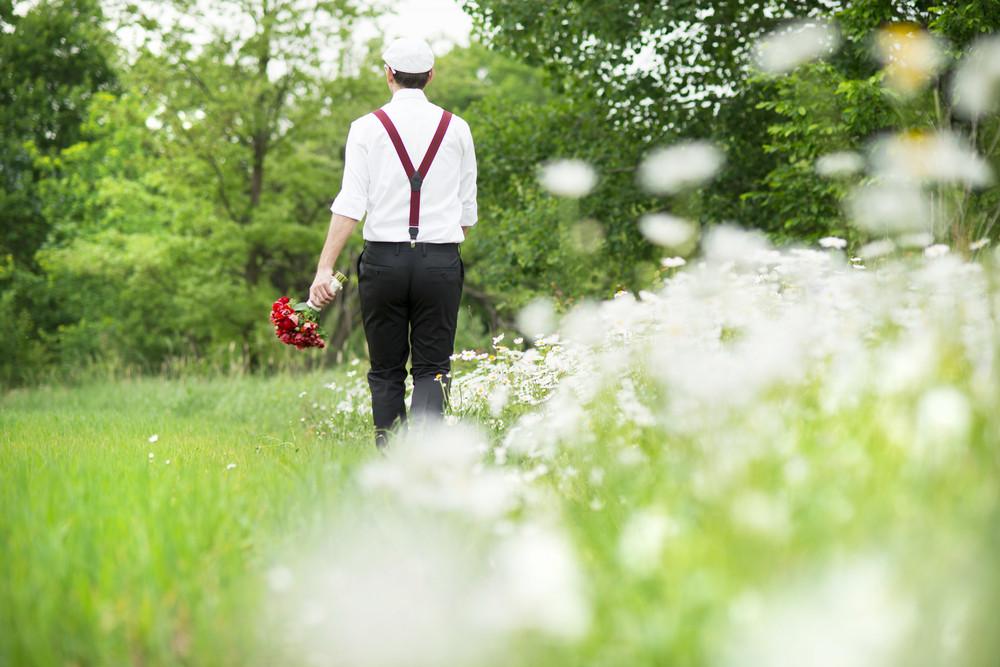Portrait of handsome groom in the dandelion flower field in green park.