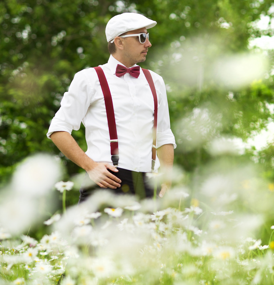 Portrait of handsome groom in the dandelion flower field in green park.