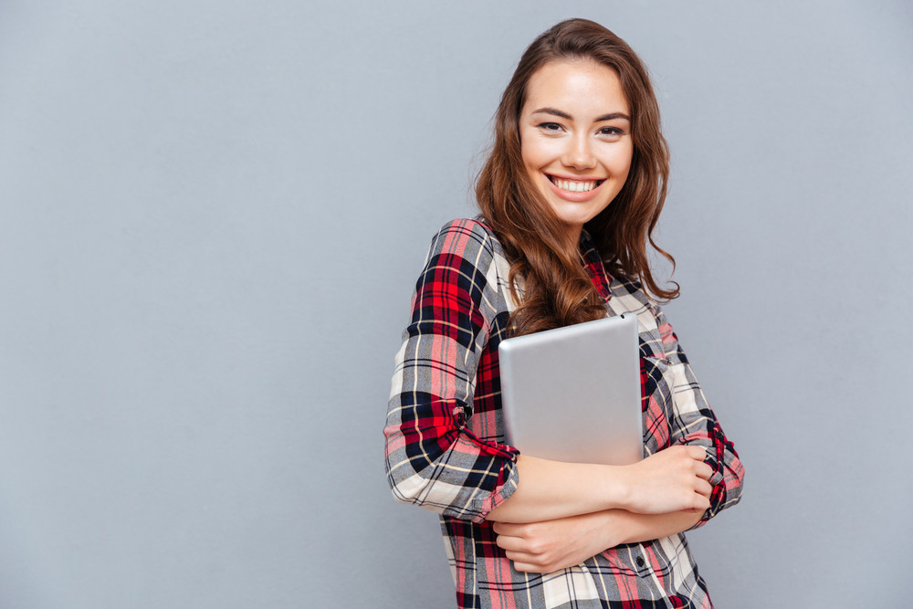 Portrait of happy attractive young woman in checkered shirt holding tablet over grey background