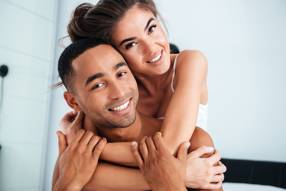 Portrait of happy beautiful young couple smiling and embracing at home