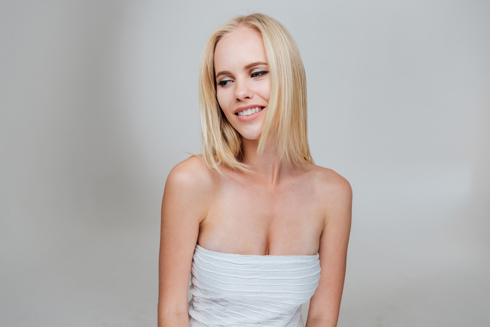 Portrait of happy beautiful young woman with blonde hair over gray background