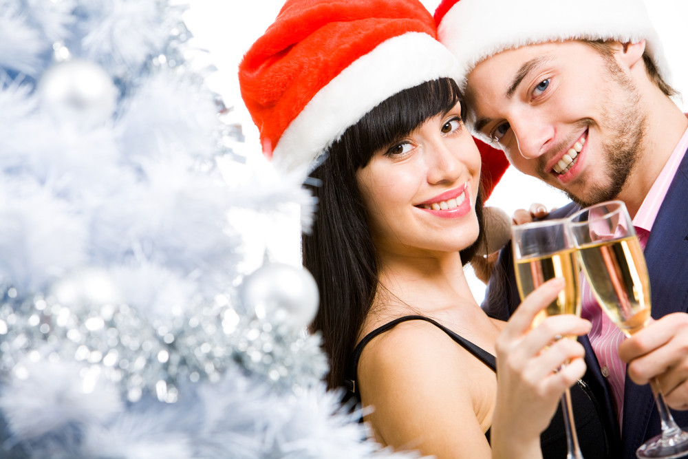 Portrait of happy couple with champagne looking at camera and smiling