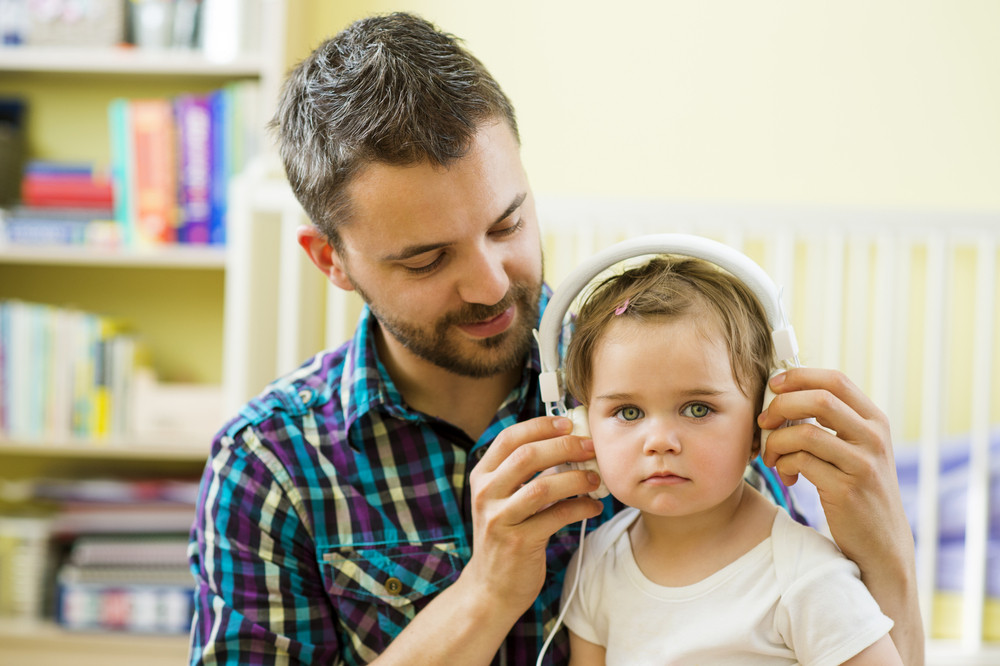 Portrait of happy father and his little daughter listening to music with headphones