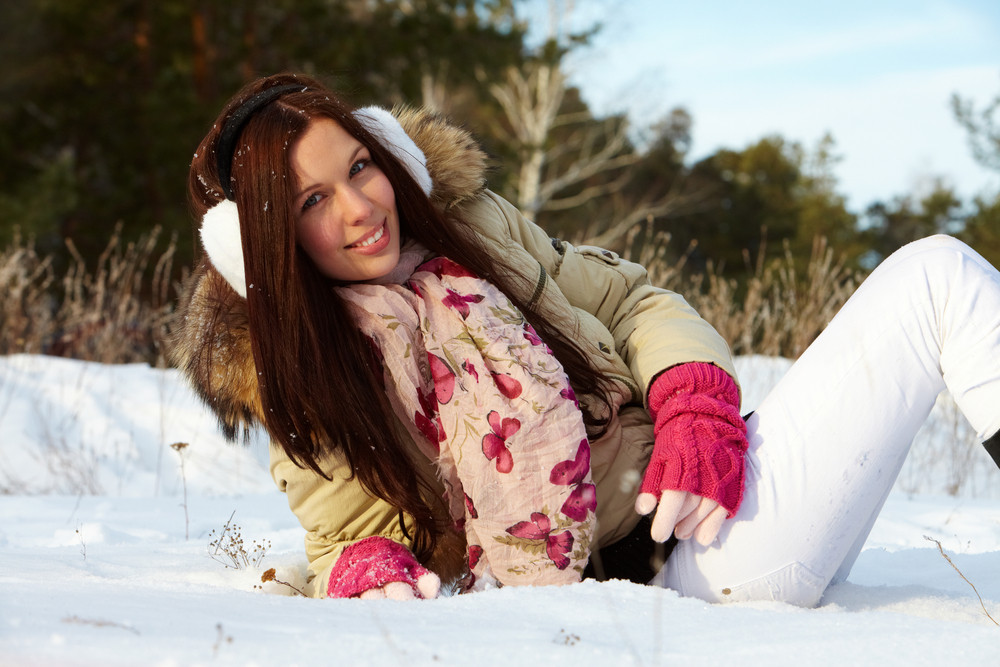 Portrait of happy girl lying on snow and looking at camera