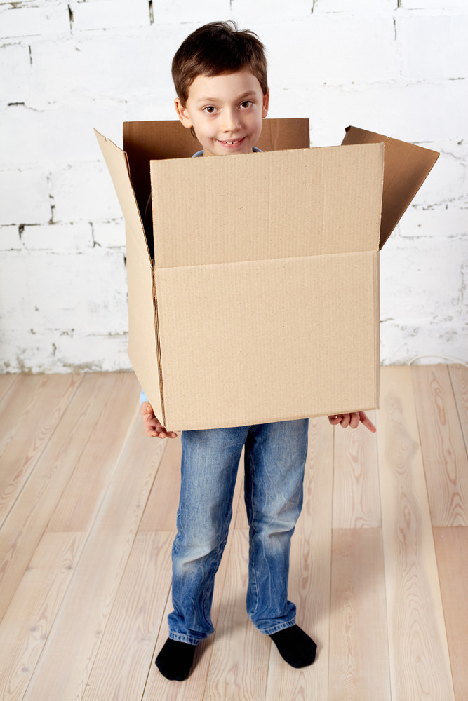 Portrait of happy kid in box looking at camera