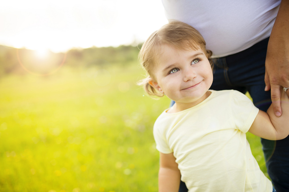Portrait of happy little daughter holding her pregnant mother´s hand in the park