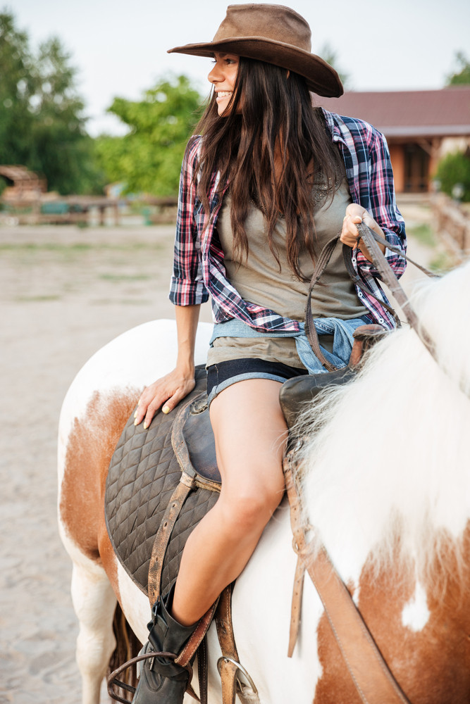 Portrait of happy lovely young woman cowgirl riding horse on ranch
