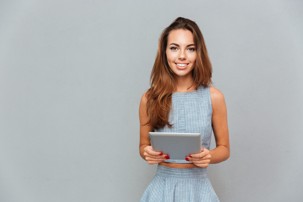 Portrait of happy lovely young woman standing and using tablet over grey background