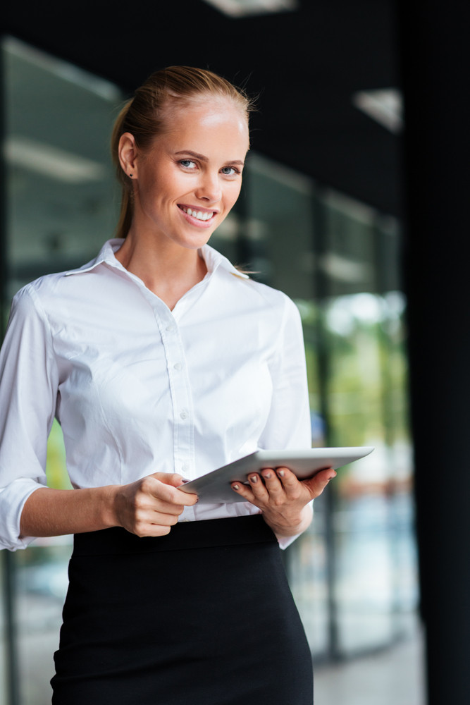 Portrait of happy smiling businesswoman using digital tablet standing by glass building outdoors