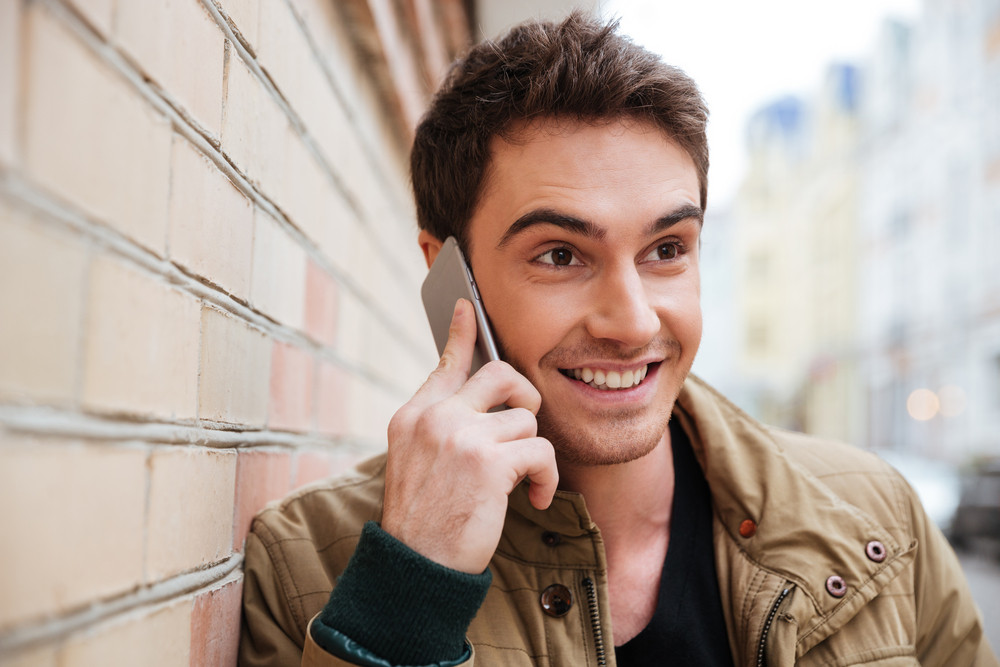Portrait of happy young man walking on the street and looking aside while talking by his phone.