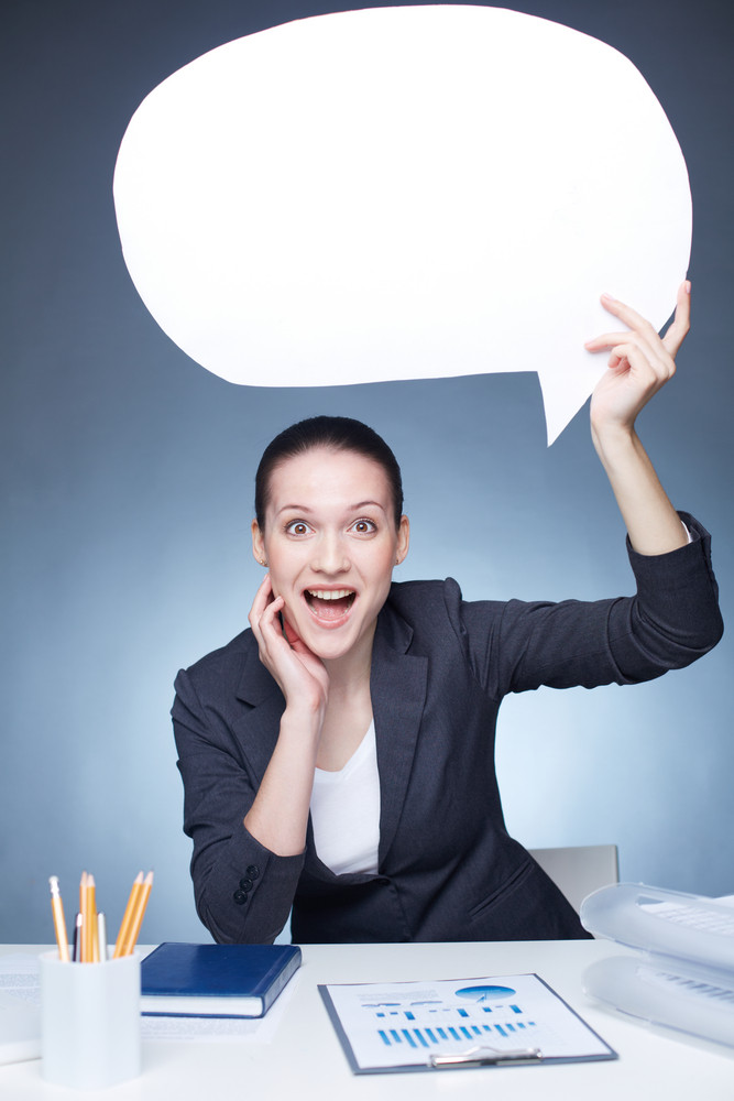 Portrait of joyful businesswoman holding paper speech bubble while sitting at workplace