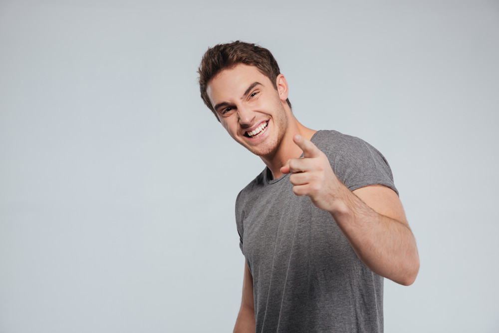Portrait of laughing brunette man pointing finger at camera isolated on the gray background