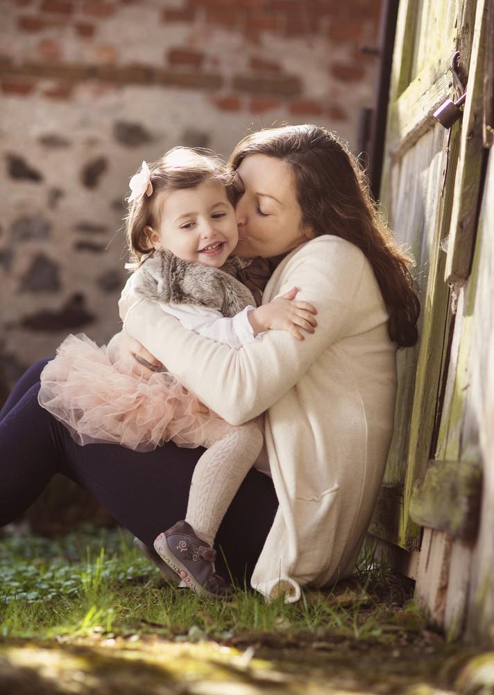 Portrait of little girl kissing her pregnant mother