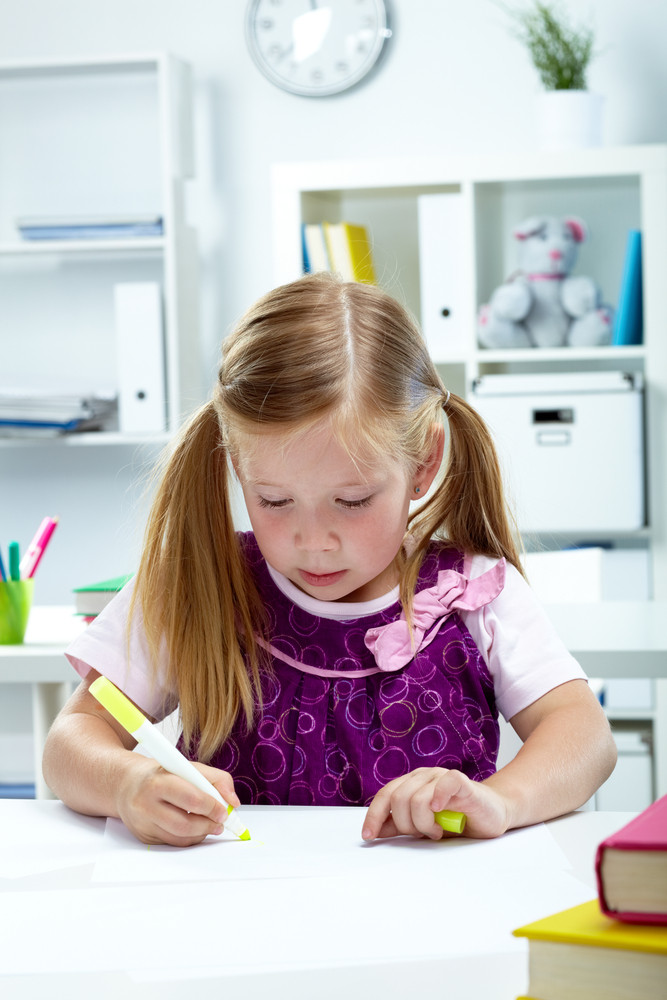 Portrait of lovely girl drawing with yellow highlighter