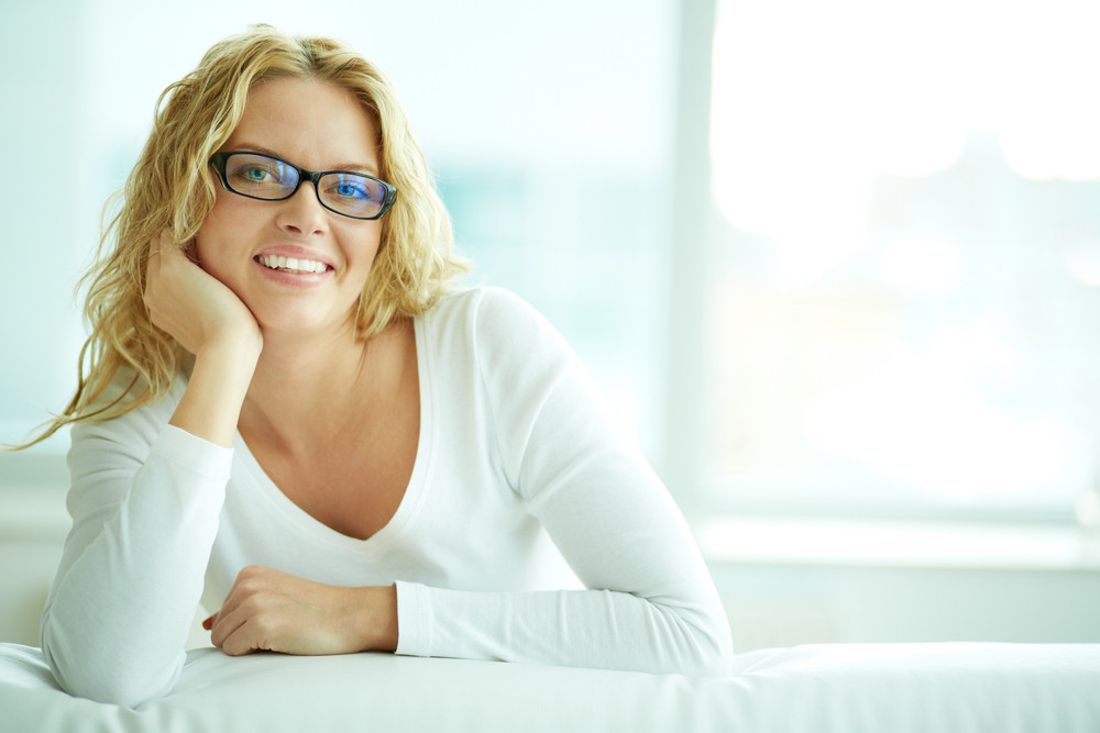 Portrait of lovely woman in eyeglasses looking at camera with smile