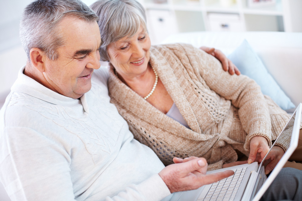 Portrait of mature man and his wife working with laptop at home