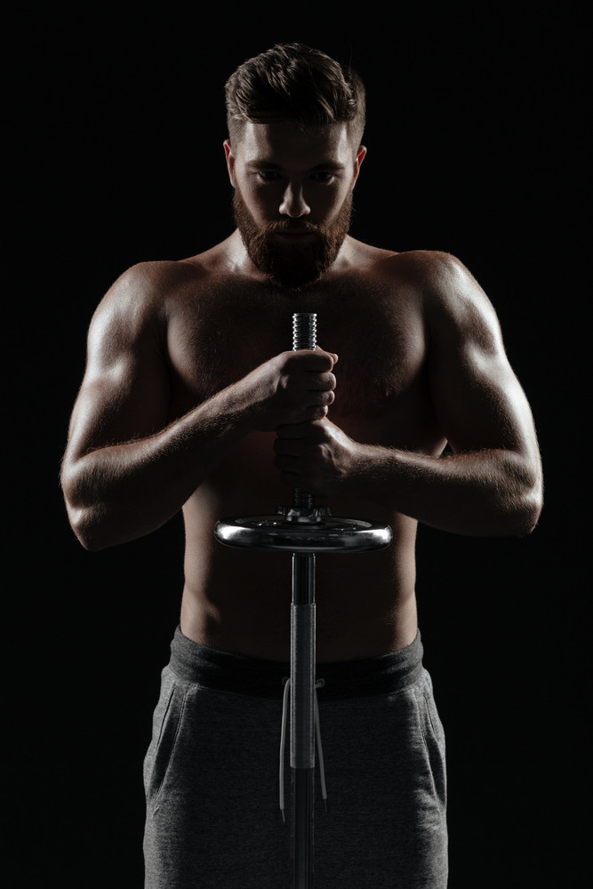 Portrait of naked athletic man with barbell. isolated dark background