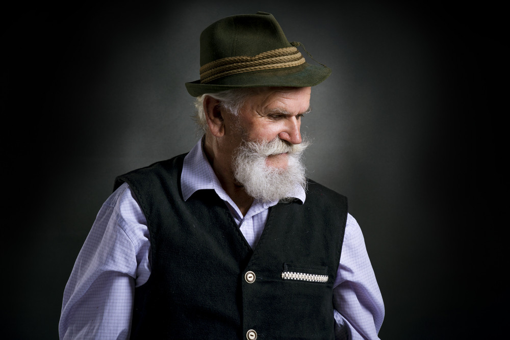 Portrait of old bearded bavarian man in traditional felt hat, posing in studio on black background