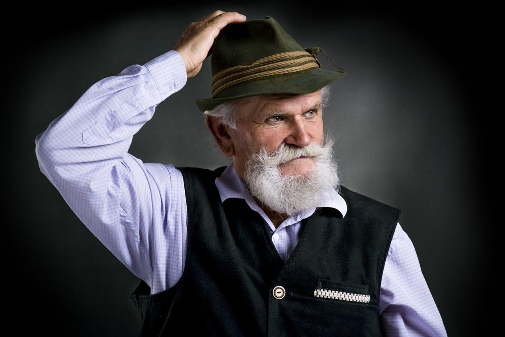 Portrait of old bearded bavarian man in traditional felt hat, posing in studio on black background