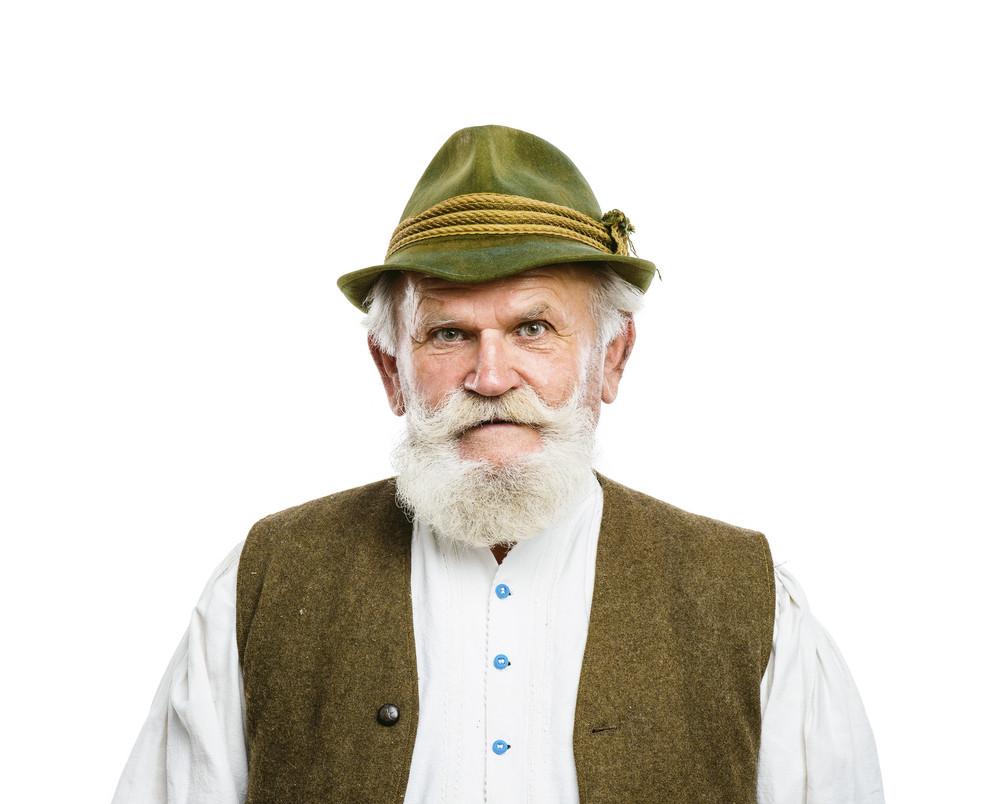 Portrait of old bearded bavarian man in traditional felt hat, posing in studio on white background