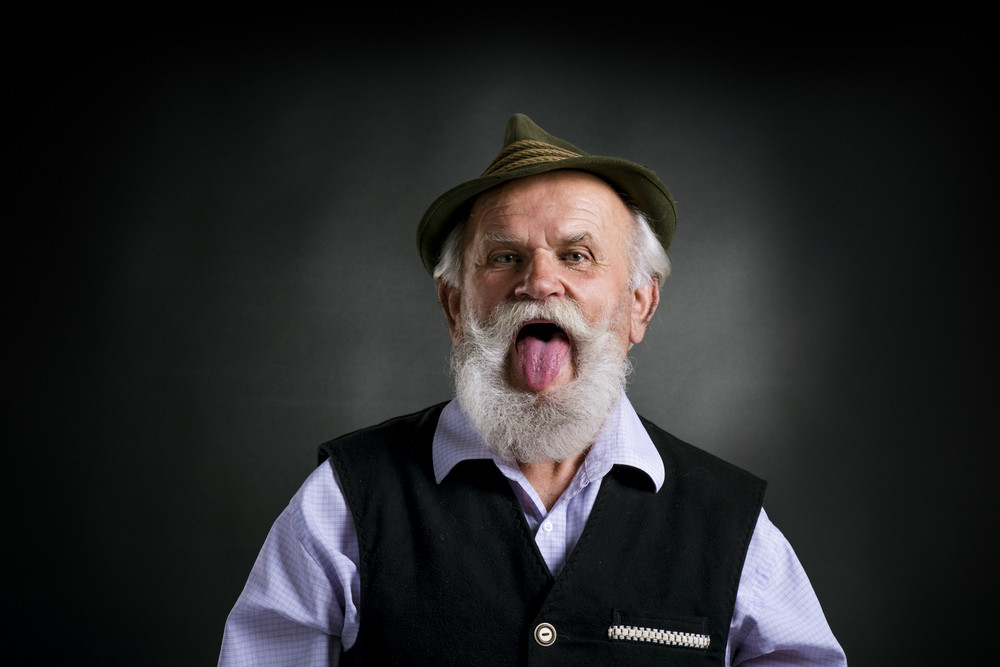 Portrait of old bearded bavarian man in traditional felt hat, sticking his tongue out in studio on black background