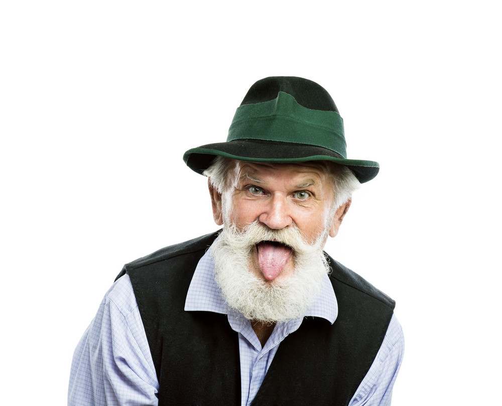 Portrait of old bearded bavarian man in traditional felt hat, sticking his tongue out in studio on white background