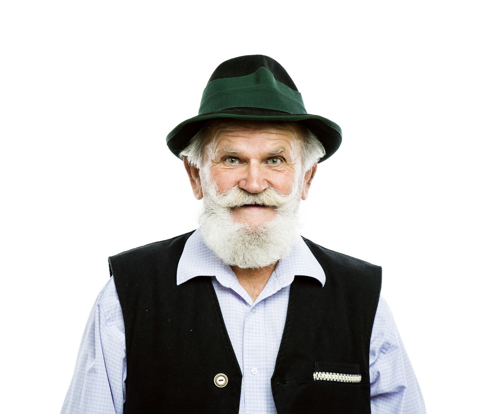 Portrait of old bearded bavarian man in traditional hat, isolated on white background