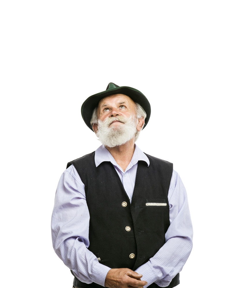 Portrait of old bearded bavarian man in traditional hat looking upwards isolated on white background
