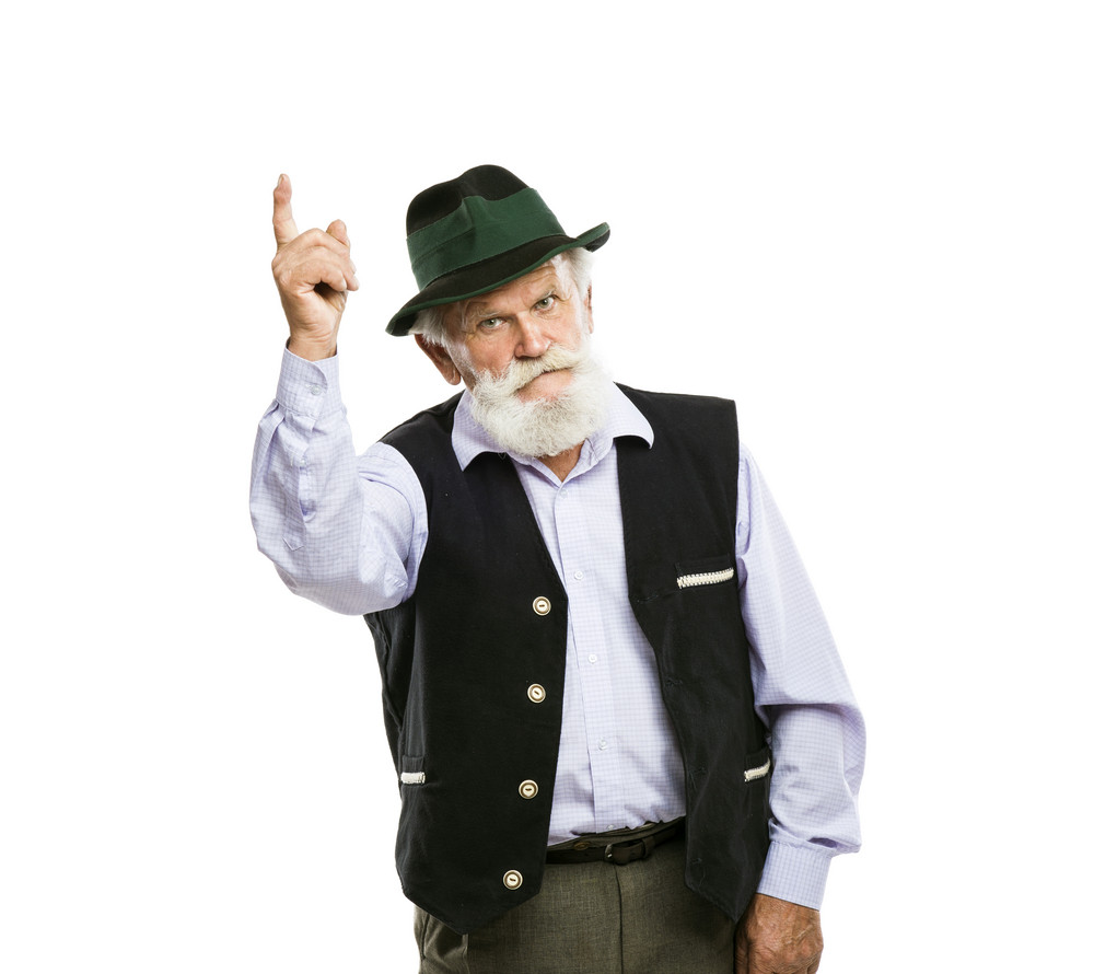 Portrait of old bearded bavarian man in traditional hat pointing upwards isolated on white background