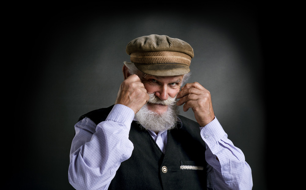 Portrait of old bearded man in traditional cap holding his moustache, posing in studio on black background