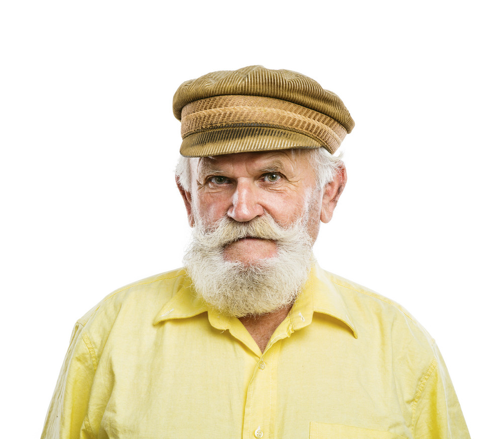 Portrait of old bearded man in traditional cap, posing in studio on white background