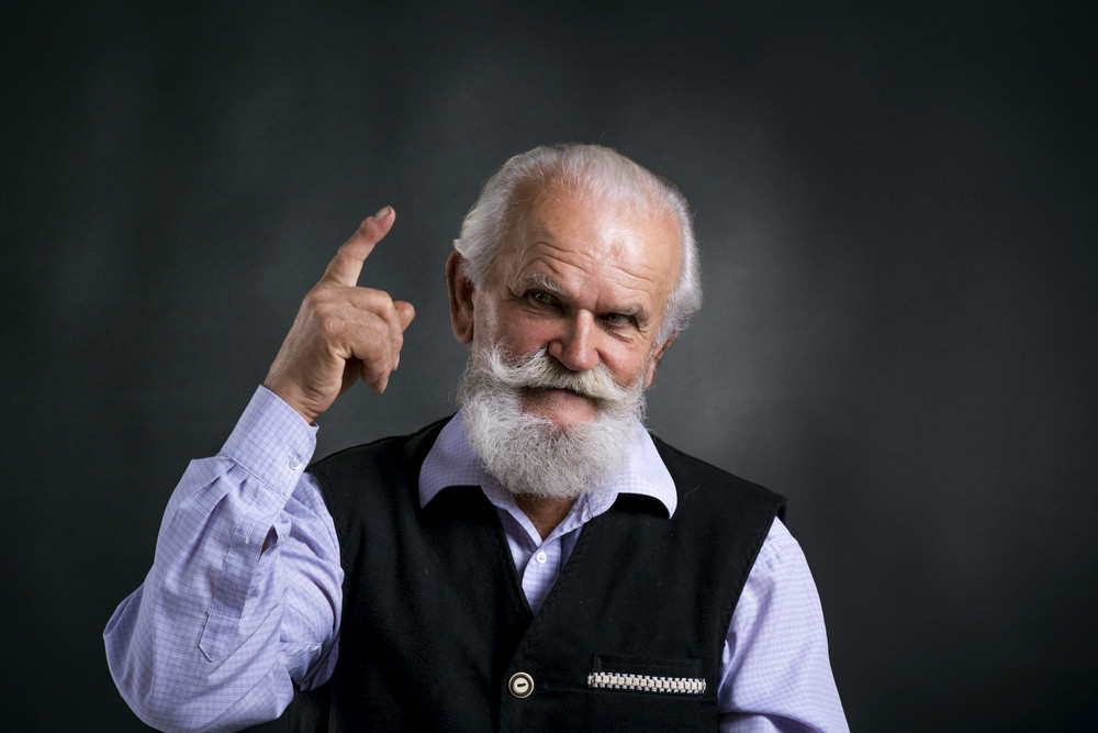 Portrait of old bearded man, posing in studio on black background
