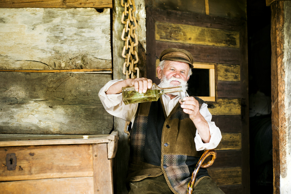 Portrait of old farmer with beard and hat having a shot of herbal spirit