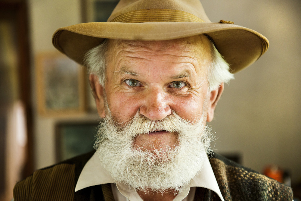 Portrait of old farmer with beard and hat