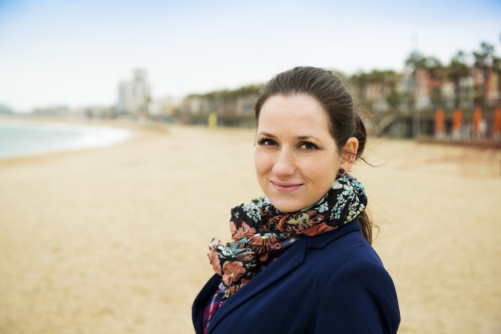 Portrait of pretty young traveler on the beach on a cold day.