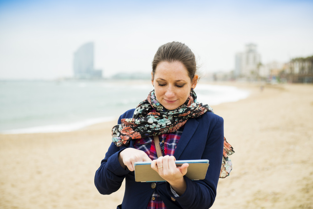 Portrait of pretty young traveler with digital tablet on the beach on a cold day.