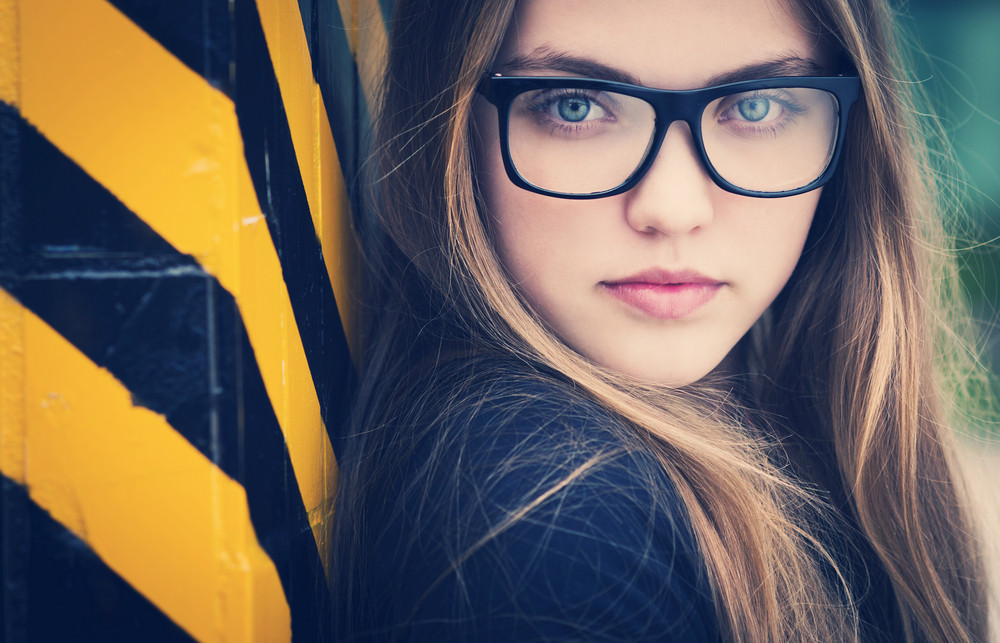 Portrait of sad teenage hipster girl standing by the black and yellow striped warning wall