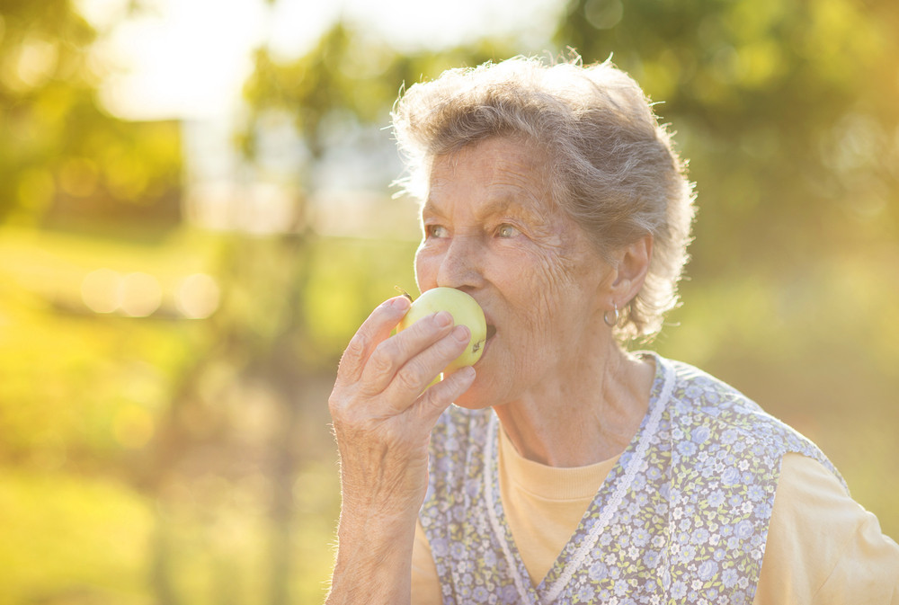 Portrait of senior woman in apron eating apple in the sunny garden