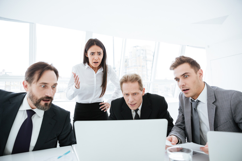 Portrait of shocked business team by the table looking at laptop in office