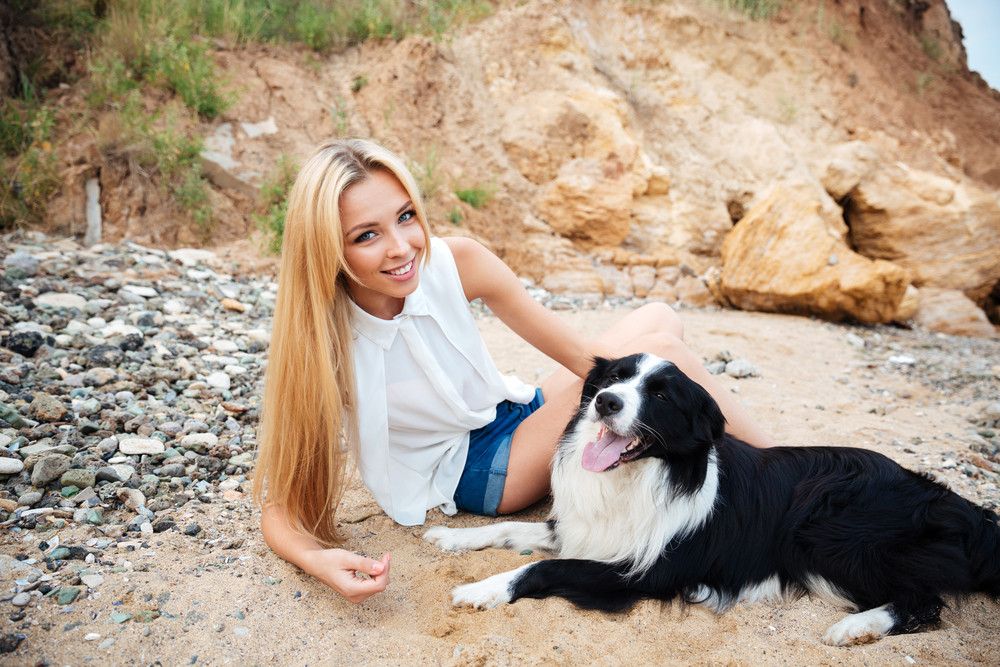 Portrait of smiling attractive young woman with dog on the beach
