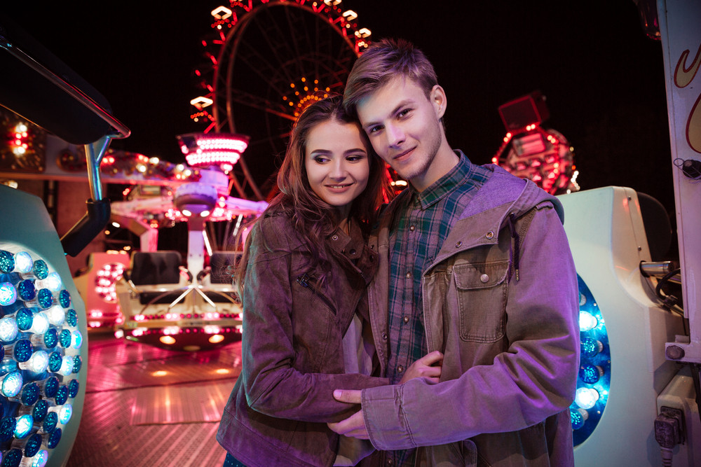 Portrait of smiling beautiful young couple standing togetehr in amusement park