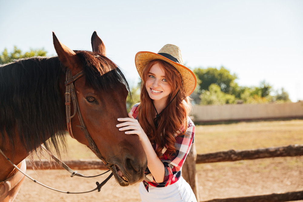 Portrait of smiling beautiful young woman cowgirl with her horse on farm
