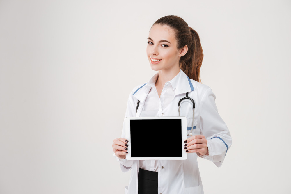 Portrait of smiling beautiful young woman doctor with blank screen tablet over white background