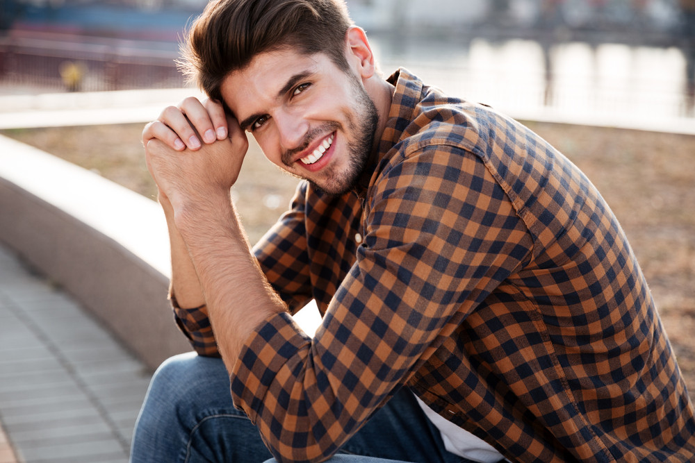 Portrait of smiling handsome young man in plaid shirt sitting outdoors