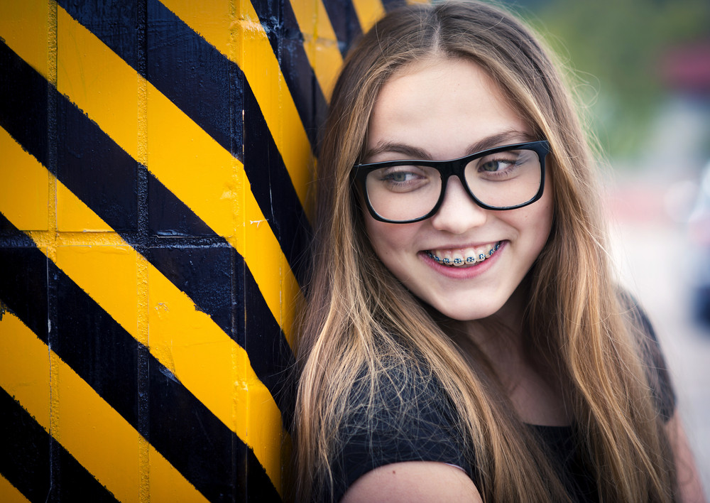Portrait of smiling teenage hipster girl standing by the black and yellow striped warning wall